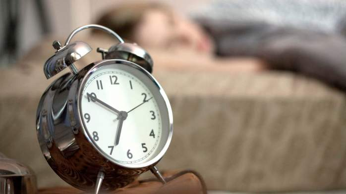 Close up of alarm clock, woman in background.